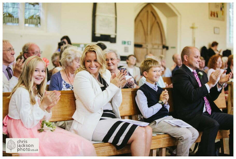 wedding ceremony guests reaction clapping smiling york heslington church wedding day weddings documentary york wedding photographer chris and hazel wedding photography