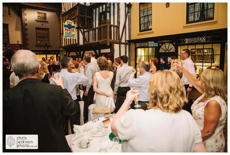 guests clapping raising glass toast speech wedding breakfast old victorian street set wedding venue york castle museum wedding photography wedding photographer York chris & hazel wedding photography