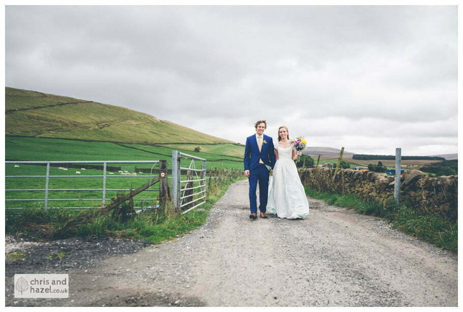 bride and groom walking down farm track portraits wedding photography with peak district in background cat wood swineshaw reservoir little padfield The venue at Wimberry hill wedding day diy vintage wedding glossop The venue at wimberry hill glossop wedding photography by Glossop wedding photographers chris and hazel natasha thorley jake rowarth