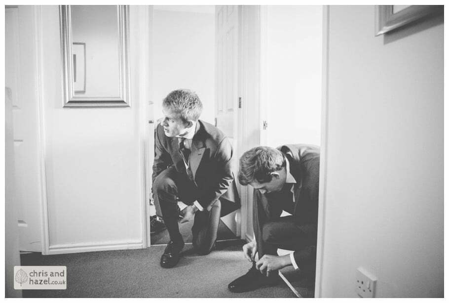 groom tying shoes with usher getting ready preparations york city centre documentary wedding photography ben charig frankie drummond wedding photographer york wedding photography wedding winter chris and hazel wedding photography york