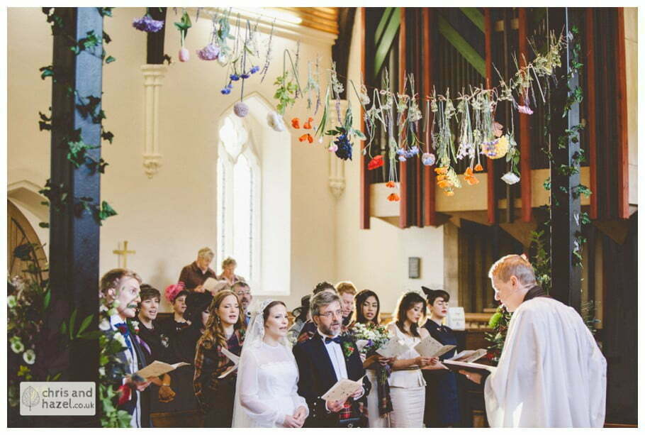 hanging flowers over alter heslington church documentary wedding photography ben charig frankie drummond wedding photographer heslington church wedding york wedding photography wedding winter chris and hazel wedding photography york