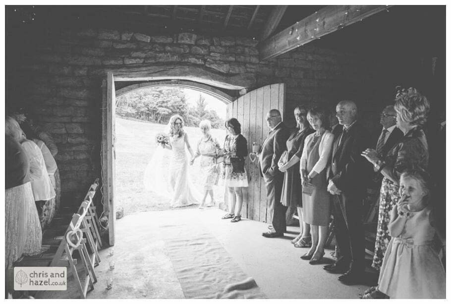 bride walking down aisle enter humanist wedding ceremony in barn documentary Wedding Photographer Harrogate Wedding Photography Braisty Estate by Chris and Hazel Wedding Photography Jonny Dunn Stef Brown