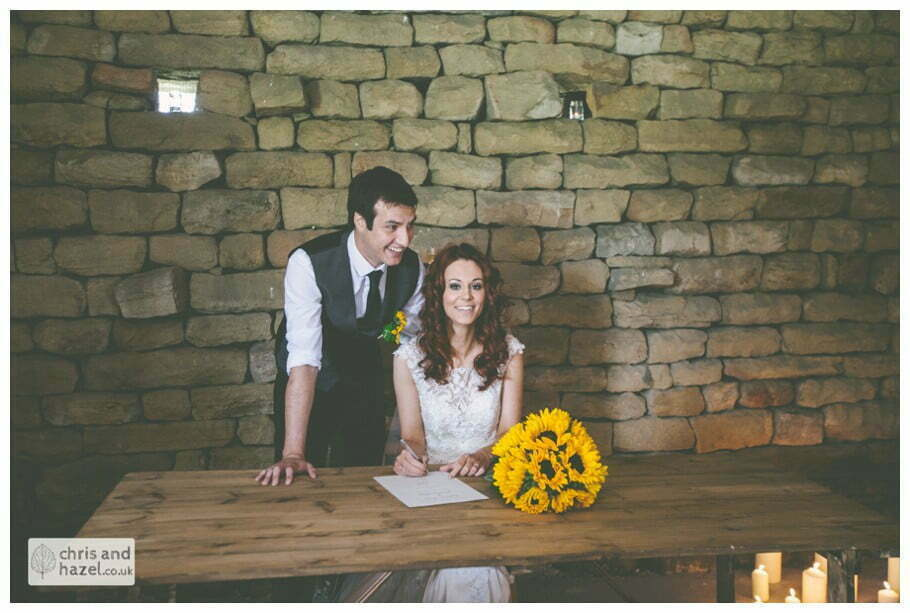 bride and groom sign register humanist wedding ceremony in barn documentary Wedding Photographer Harrogate Wedding Photography Braisty Estate by Chris and Hazel Wedding Photography Jonny Dunn Stef Brown