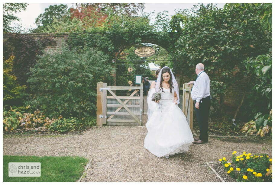 bride walking through gardens to wedding ceremony in greenhouse conservatory documentary Hull Wedding Photographer Bishop Burton College Wedding Photography Hull by Chris and Hazel Wedding Photography Ross laurelin Matulis