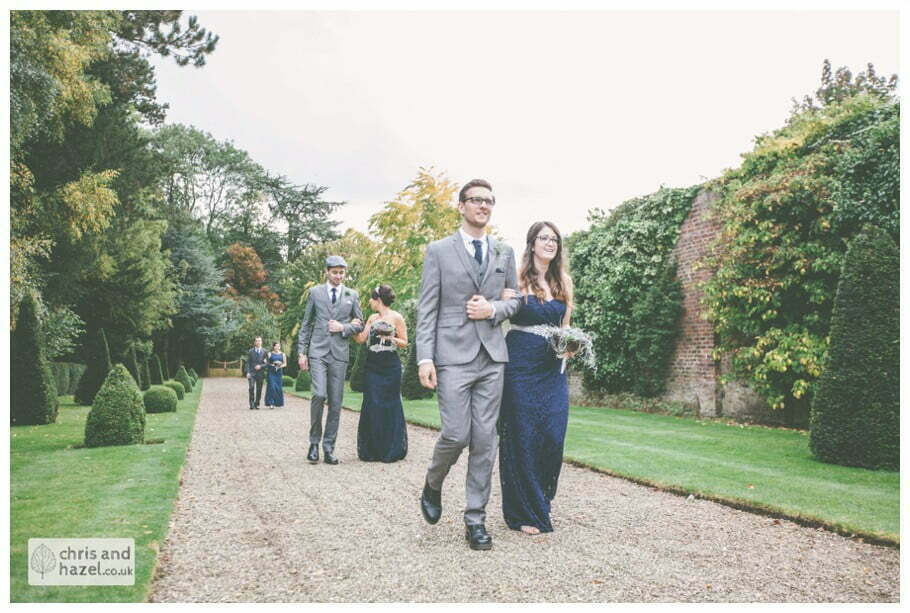 bridesmaid walking with groomsmen down aisle wedding ceremony in greenhouse conservatory documentary Hull Wedding Photographer Bishop Burton College Wedding Photography Hull by Chris and Hazel Wedding Photography Ross laurelin Matulis