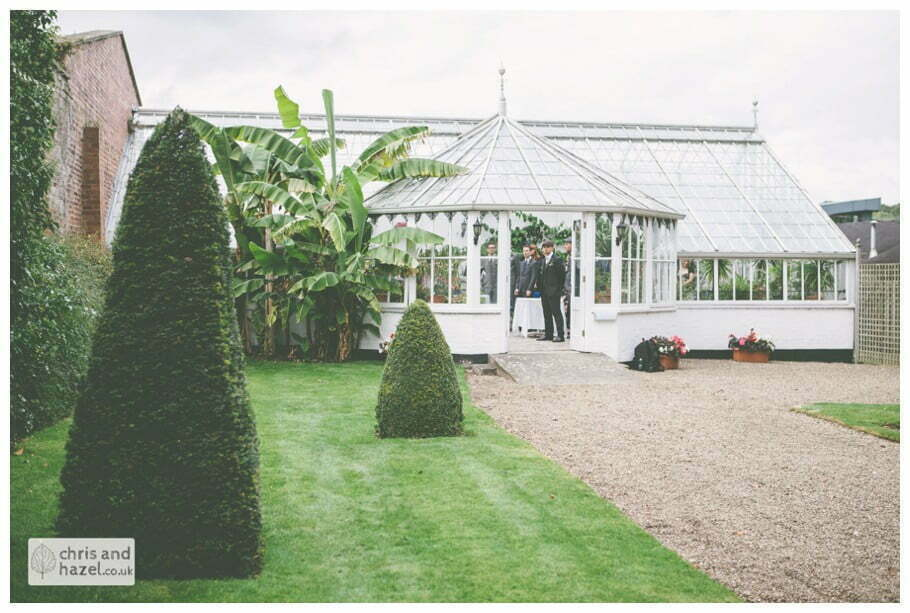 groom waiting at altar wedding ceremony in greenhouse conservatory documentary Hull Wedding Photographer Bishop Burton College Wedding Photography Hull by Chris and Hazel Wedding Photography Ross laurelin Matulis