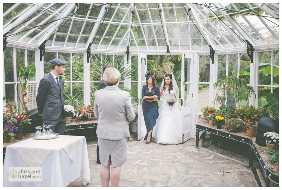 bride walking with mother of bride down aisle wedding ceremony in greenhouse conservatory documentary Hull Wedding Photographer Bishop Burton College Wedding Photography Hull by Chris and Hazel Wedding Photography Ross laurelin Matulis