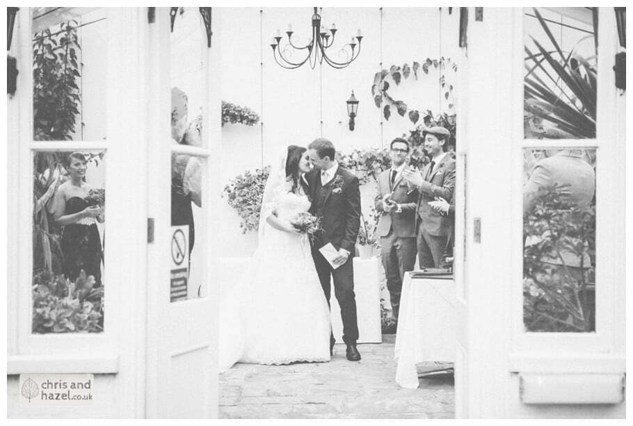 bride and groom first kiss wedding ceremony in greenhouse conservatory documentary Hull Wedding Photographer Bishop Burton College Wedding Photography Hull by Chris and Hazel Wedding Photography Ross laurelin Matulis