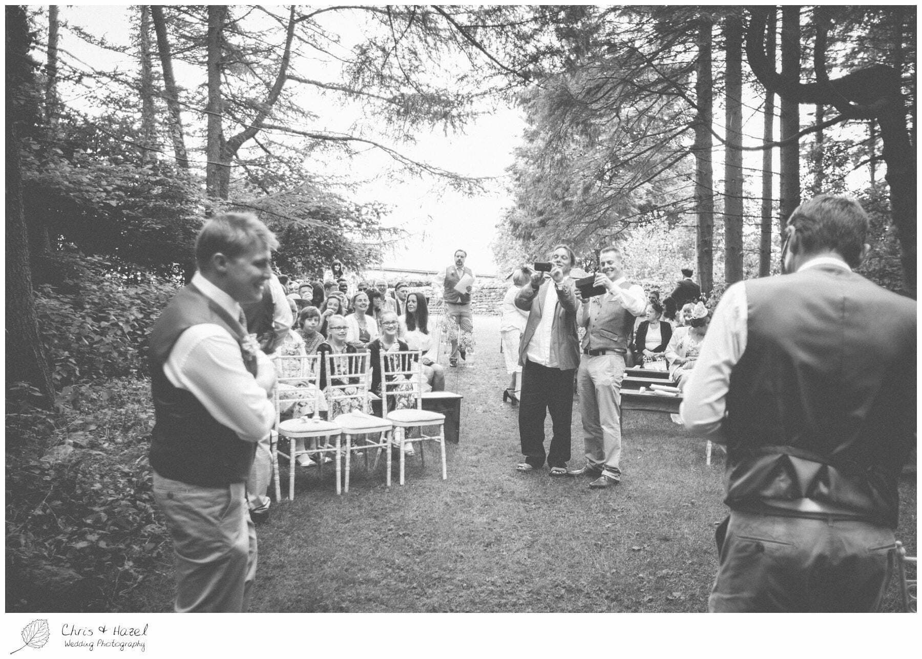 guests taking photographs, woodland, forest, ceremony, outdoor, forest wedding, woodland wedding, eco wedding, love letters, wedding, Eccup Wedding Photographer, Lineham Farm, Wedding Photography Leeds, Chris and Hazel Wedding Photography, Richard Wyatt, Laura Kelly